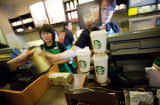 Servers help customers at a Starbucks Corp. store in Beijing, China, on Tuesday, March 8, 2011.